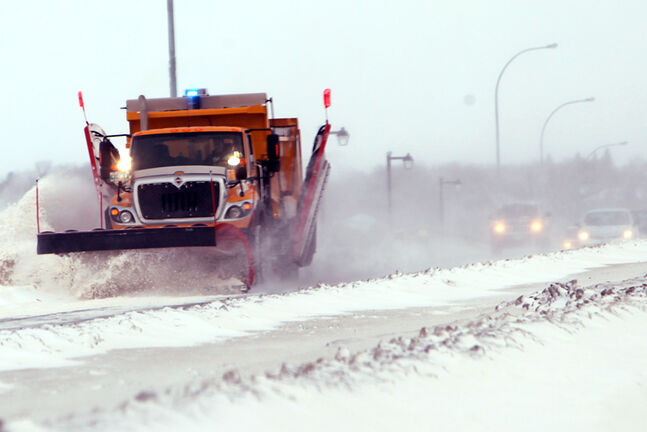 A provincial road crew clears a path along Eighteenth Street on the Thompson Bridge, last weekend.