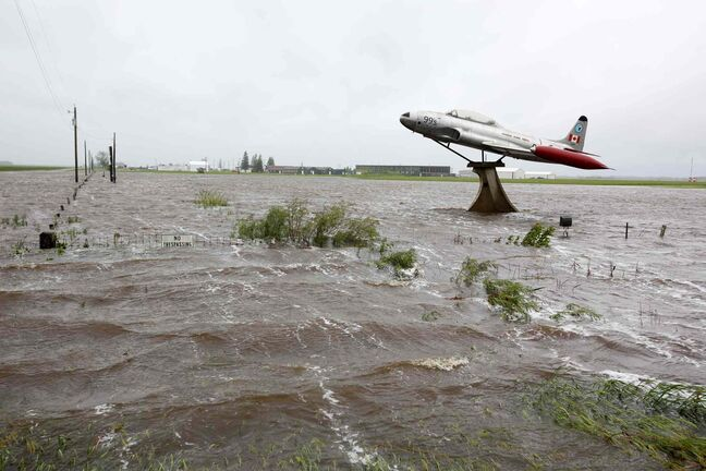 Flood waters surround a T33 fighter jet on display along Highway 10 and Sandison Road near the Brandon Municipal Airport on Sunday after rain fell almost non-stop throughout the weekend. The airport was closed due to the flooding.
