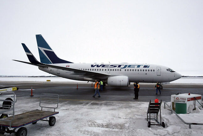 In this January 2006 photo, ground crew work on a WestJet plane at the Brandon Municipal Airport.