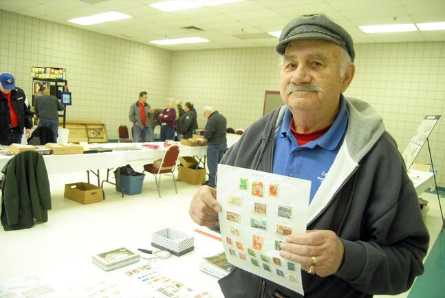 Stamp collector Bob Wright holds up a page of stamps he had for sale at the Prairie Mountain Philatelic Society's debut event at the Keystone Centre on Saturday. They are duplicates of stamps he has back at home.