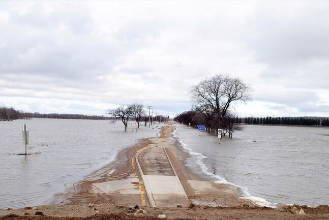 Floodwater begins to recede off Grand Valley Road — a roadway that floods over at 1,176.5 feet above sea level — on Sunday.