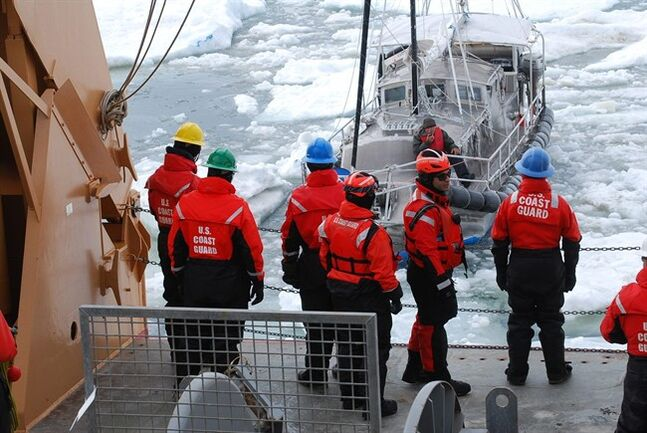 In this photo released by the U.S. Coast Guard and taken Saturday July 12, 2014, crewmembers on the Coast Guard Cutter Healy make contact with a mariner aboard his 36-foot sailboat trapped in Arctic ice approximately 40 miles northeast of Barrow, Alaska, the northernmost city in the United States. The Coast Guard freed the Canadian sailboat, the Altan Girl out of Vancouver, that was attempting to sail to eastern Canada through the Northwest Passage. (AP Photo/U.S. Coast Guard)