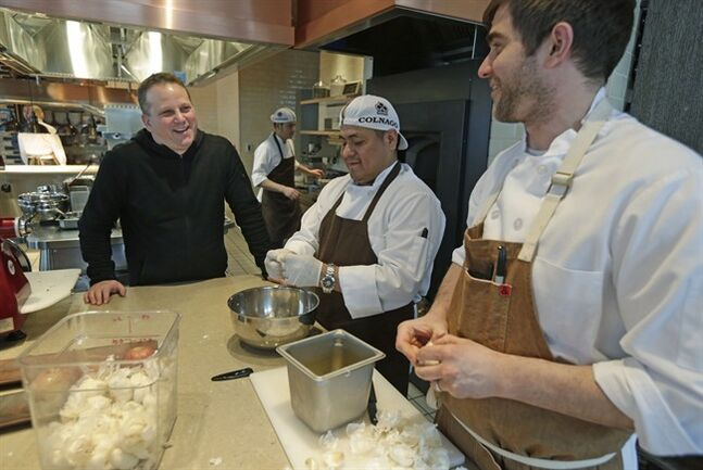 FILE - This Feb. 12, 2014 file photo shows chef Paul Kahan, left, speaking to kitchen staff at his restaurant Nico Osteria in Chicago. Kahan is one of the most award-winning chefs in America, but don't go looking for him on television. In fact, the former computer scientist turned last year's James Beard Award winner for best chef shies away from the spotlight almost entirely. Instead, he chooses to focus on his family and the handful of Chicago restaurants he runs with his partners _ nationally known eateries like Blackbird, avec and The Publican. (AP Photo/M. Spencer Green, File)