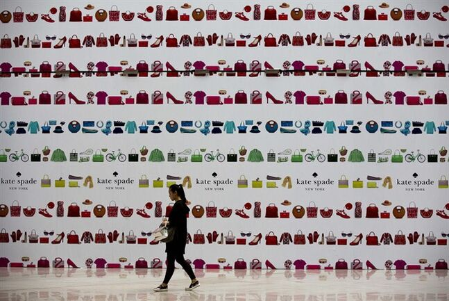 A woman walks past a fashion boutique outlet under construction covered by its advertisement board at a shopping mall in Beijing, China Monday, May 12, 2014. Chinese president Xi Jinping has told the country to get used to slower growth, damping expectations of a new stimulus, following weakening trade and manufacturing. Economic growth slowed in the latest quarter to 7.4 percent after last year's full-year expansion of 7.7 percent tied 2012 for the weakest performance since 1999. (AP Photo/Andy Wong)