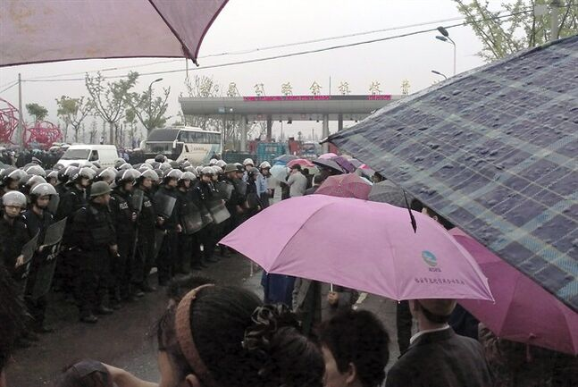 In this Sunday, May 11, 2014 photo released by Hong, Chinese police with shields stand guard near the toll of a highway during a protest against the construction of a waste incinerator in Yuhang district, Hangzhou in China's Zhejiang province. Government pledges to seek public approval for a planned waste incinerator in eastern China failed to appease the project's neighbors Monday, May 12, 2014 after thousands of them, concerned over potential health hazards, blocked the highway and clashed with police in a bid to stop the construction. (AP Photo/Hong)