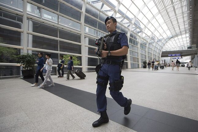 An Airport Police Special Force officer patrols at Hong Kong airport, Friday, June 6, 2014. Hong Kong's airlines and airport are on alert after receiving a warning from Taiwan that a woman in mainland China may be planning to board a flight to the Asian financial hub with a bomb. (AP Photo/Kin Cheung)