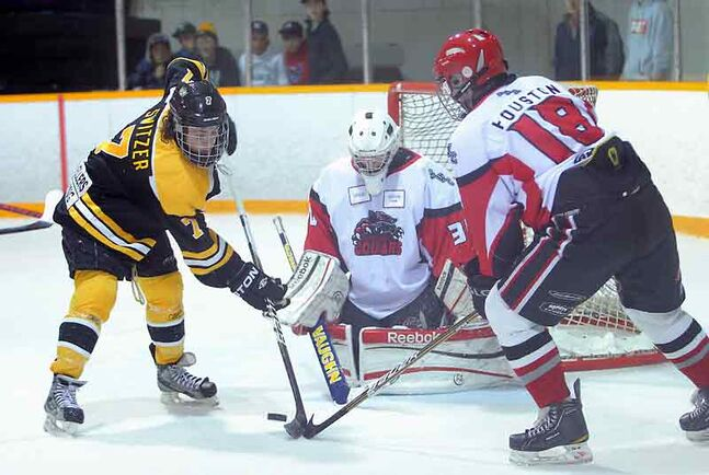 Brandon Switzer (7) of the Brandon Wheat Kings jousts for the puck with Sam Houston of the Southwest Cougars in front of Cougars goalie Tyson Verhelst at the Sportsplex on Friday.