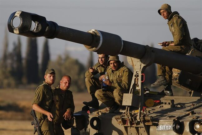 Israeli soldiers gather for a break on a mobile artillery unit at a position on the Israel-Gaza border, Friday, July 11, 2014. Gaza rocket fire struck a gas station and set it ablaze Friday in southern Israel, seriously wounding one person as rocket fire also came from Lebanon for the first time in the four-day-long offensive. Rocket fire by Palestinian militants continued from Gaza toward various locations in southern Israel. (AP Photo/Lefteris Pitarakis)