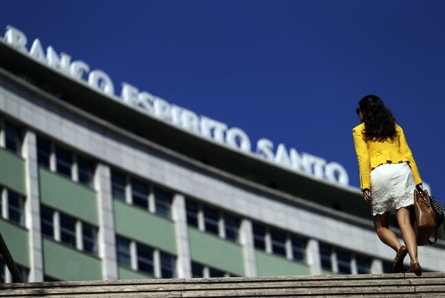 A woman exits a subway station next to a Portuguese bank Banco Espirito Santo's offices building, in Lisbon, Monday, Aug. 4, 2014. Portugal's biggest banking scandal, which compelled authorities Sunday to put up euro 4.9 billion ($6.6 billion) to prevent the collapse of ailing Banco Espirito Santo, raised key questions about how regulators were apparently hoodwinked and focused minds on the European banking system stress tests, whose results are due in October. (AP Photo/Francisco Seco)