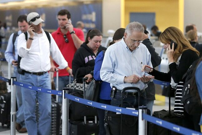 Passengers at O'Hare International Airport wait in a United Airlines ticketing line Tuesday, May 13, 2014, in Chicago. Smoke in a regional radar facility forced a halt to all incoming and outgoing flights at both of Chicago's airports. The Federal Aviation Administration says all its personnel were evacuated from the Chicago Terminal Radar Approach Control, or TRACON, facility in suburban Elgin at around 11:30 a.m. Tuesday.(AP Photo/Charles Rex Arbogast)
