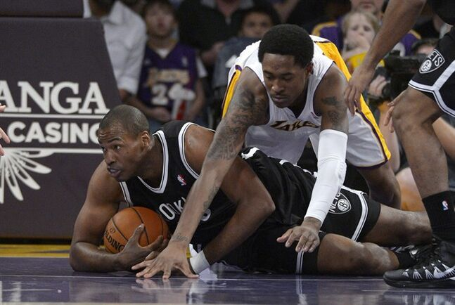 Brooklyn Nets center Jason Collins, left, battles for a loose ball with Los Angeles Lakers guard MarShon Brooks during the first half of an NBA basketball an NBA basketball game, Sunday, Feb. 23, 2014, in Los Angeles. (AP Photo/Mark J. Terrill)