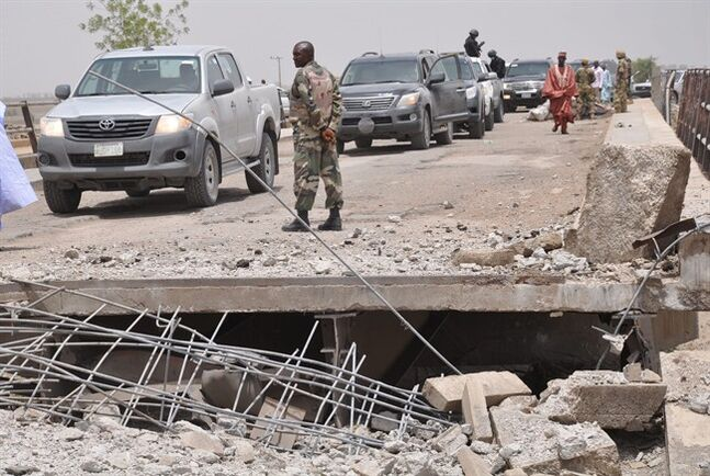 In this photo taken Sunday May 11, 2014. A soldier and other government officials inspect the bridge that was bombed following an attack by Islamic militants last week in Gambaru, Nigeria. Many brutalized residents of the once bustling town of Gamboru say they are moving across the border to Cameroon because they cannot trust the Nigerian government to protect them, after repeated attacks by Islamic militants, including an attack a few days ago that killed some hundreds of people with more than 1,000 shops, dozens of homes and 314 trucks and cars bombed and burned out. (AP Photo/Jossy Ola)