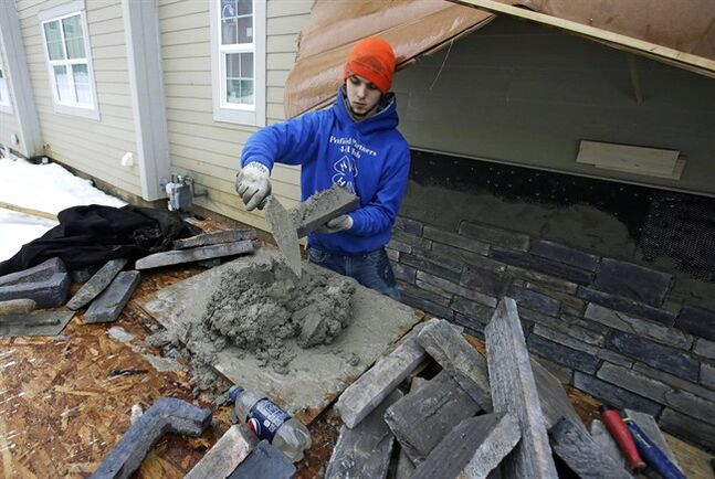 In this Jan. 10, 2014, photo, Trevor Davis puts concrete on stone for the foundation of a new home, in Pepper Pike, Ohio. The National Association of Home Builders reports on sentiment among U.S. builders on Tuesday, Feb. 18. (AP Photo/Tony Dejak)