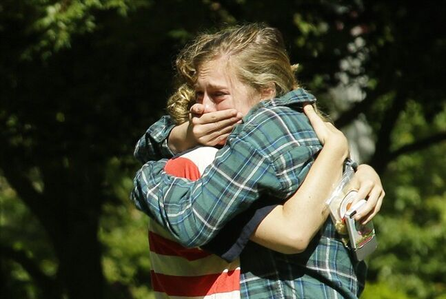 Two women embrace near a prayer circle on the campus of Seattle Pacific University, Friday, June 6, 2014 in Seattle. Classes were cancelled Friday following a shooting at Otto Miller Hall Thursday afternoon. A 19-year-old man was fatally shot and two other young people were wounded after a gunman entered the foyer and started shooting. Aaron R. Ybarra, 26, was booked into the King County Jail late Thursday for investigation of homicide, according to police and the jail roster. (AP Photo/Ted S. Warren)