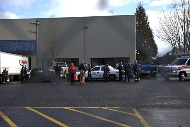 Police secure the scene of a shooting at a business park in the Fruit Valley neighborhood of Vancouver, Wash. on Monday Feb. 3, 2014. Police say at least one person was shot just before noon Monday at a Benjamin Moore Paint store in the area. (AP Photo/The Columbian, Zachary Kaufma)