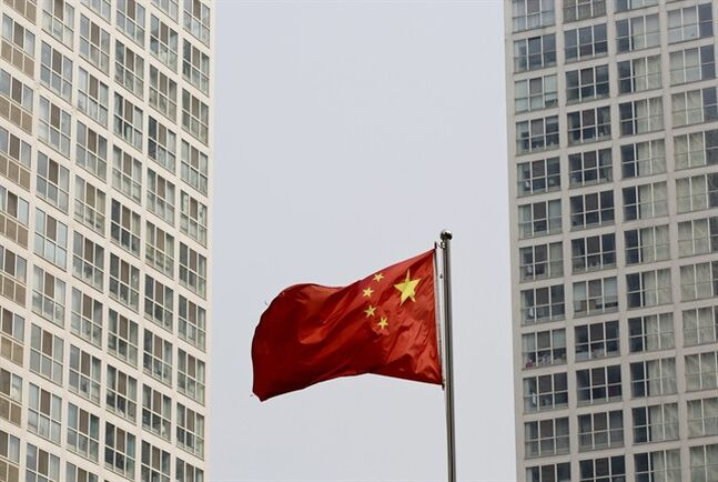 A Chinese national flag flutters in the wind in between a high-rise residential and office complex in Beijing, China Monday, May 19, 2014. Asian stock markets were mostly lower Monday after China reported a weak increase in housing prices. The Chinese government is trying to restrain surging housing costs with lending and other curbs. But any weakness in sales prompts fears of repercussions for other industries and possible debt problems if developers default on loans. (AP Photo/Andy Wong)