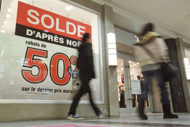 A man and a woman walks by a store offering big discounts on Boxing Day in Montreal, on December 26, 2012. THE CANADIAN PRESS/Graham Hughes.