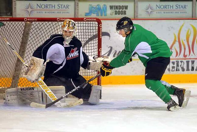 Nick Buonassisi tries to beat goaltender Curtis Honey during the Brandon Wheat Kings' practice Thursday at Westman Place.