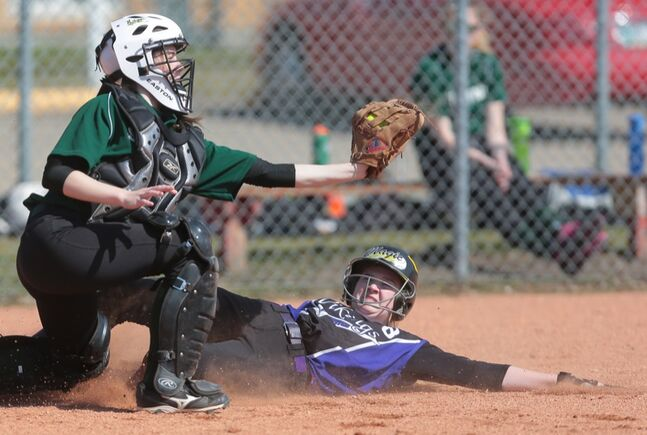Taylor Curtis slides into home plate beating the throw to Neelin's Kirsten Brown during Thursday's high school fastball finals at Vincent Massey. (Bruce Bumstead/Brandon Sun)