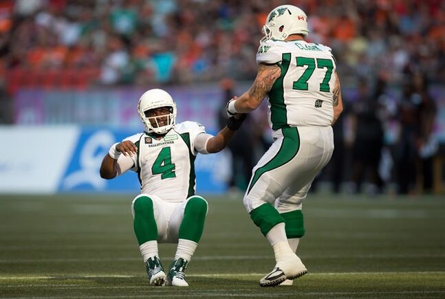 Saskatchewan Roughriders' quarterback Darian Durant, left, is helped up by Dan Clark after throwing an incomplete pass against the B.C. Lions during the first half of a CFL football game in Vancouver, B.C., on Sunday August 24, 2014. THE CANADIAN PRESS/Darryl Dyck