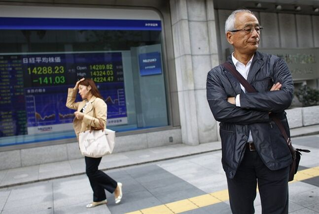 A man stands await crossing a street outside a securities firm in Tokyo, Monday, April 28, 2014. Shares fell Monday in Asia as investors remained wary of mounting violence in Ukraine, while awaiting a raft of financial indicators due later in the week. Japan's benchmark Nikkei 225 stock index fell 1.2 percent to 14,257.37. (AP Photo/Junji Kurokawa)