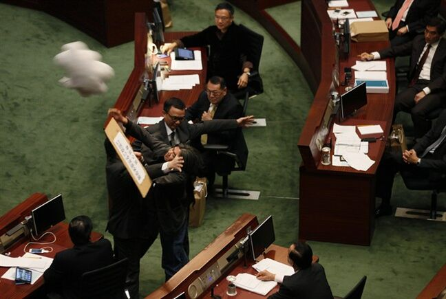 Security guards try to stop Hong Kong Legislative Council member Leung Kwok-hung, center, also known as Long Hair, throwing a slogan to Hong Kong Financial Secretary, John Tsang when Tsang delivers his budget speech at the Legislative Council in Hong Kong Wednesday, Feb. 27, 2013. Leung demanded government to set up a universal retirement protection scheme for elderly. (AP Photo/Kin Cheung)