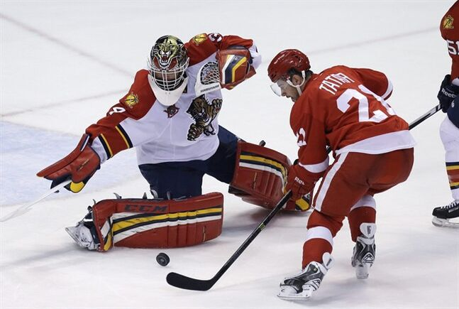 Florida Panthers goalie Tim Thomas (34) deflects a shot by Detroit Red Wings left wing Tomas Tatar (21) of Slovakia, during the third period of an NHL hockey game in Detroit, Sunday, Jan. 26, 2014. THE CANADIAN PRESS/AP/Carlos Osorio