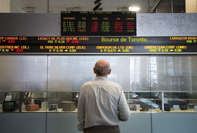 A man watches the financial numbers at the TMX Group in Toronto's financial district in a May 9, 2014 photo. THE CANADIAN PRESS/Darren Calabrese