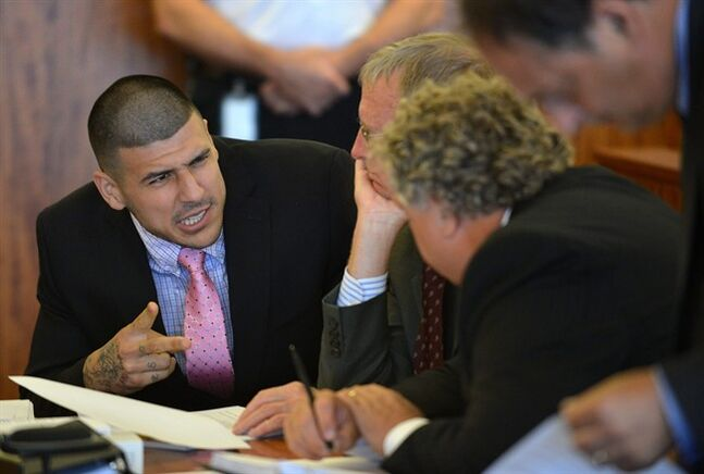 Aaron Hernandez, left, speaks with his lawyers, Charles Rankin, center, and Michael Fee during a hearing in Fall River superior court Monday, July 7, 2014, in Fall River, Mass. The Judge agreed that Hernandez could be moved to a jail closer to Boston while he awaits his trial for the murder of Odin Lloyd. (AP Photo/The Boston Globe, Josh Reynolds, Pool)