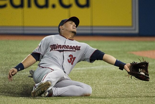 Minnesota Twins right-fielder Oswaldo Arcia makes sliding catch on a ball hit by Toronto Blue Jays Jose Bautista during sixth inning AL baseball action in Toronto on Wednesday, June 11, 2014. THE CANADIAN PRESS/Nathan Denette