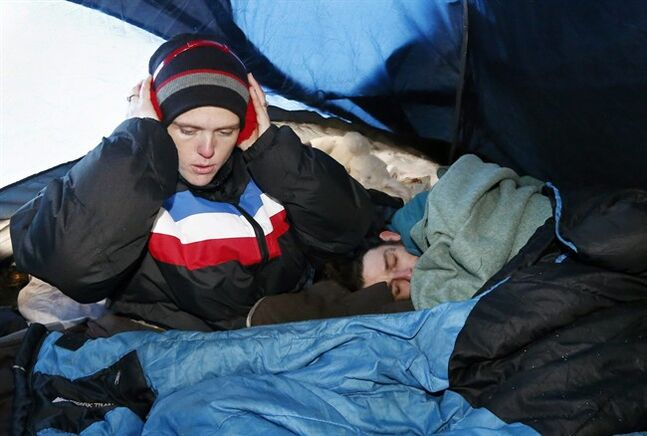 FILE - In this Dec. 6, 2013 file photo, Sarah Davis, left, puts on earmuffs over her hat as John Davis, right, burrows under some blankets, as they try to keep warm in their tent at a homeless encampment in Oklahoma City. The weather kills at least 2,000 Americans each year _ and the deaths are most common in the largest cities and the most rural areas, according to a new Centers for Disease Control and Prevention report released Wednesday, July 30, 2014. (AP Photo/Sue Ogrocki, File)