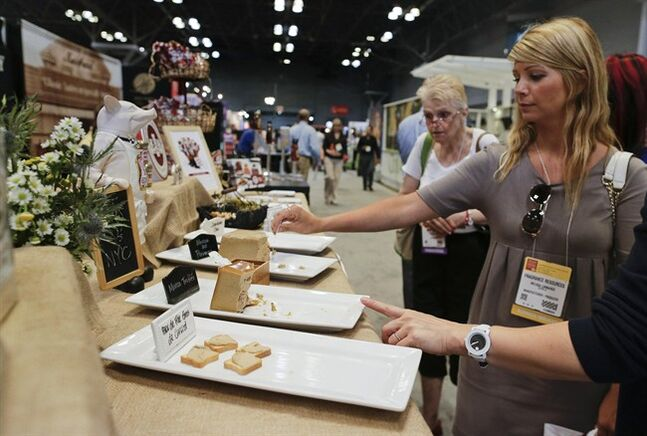 Convention-goers sample a variety of pates at the Summer Fancy Food Show specialty food convention, Tuesday, July 1, 2014, in New York. About 170,000 pounds of delicacies were donated and distributed to food pantries across the five boroughs.
