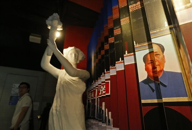 In this Wednesday, May 28, 2014 photo, a statue of the Goddess of Democracy and a portrait of the late Communist leader Mao Zedong are displayed at the June 4th Museum in Hong Kong. The 75 square meters (800 square feet) June 4th Museum is the world's only museum chronicling the brutal crackdown on the 1989 Tiananmen protests. (AP Photo/Vincent Yu)