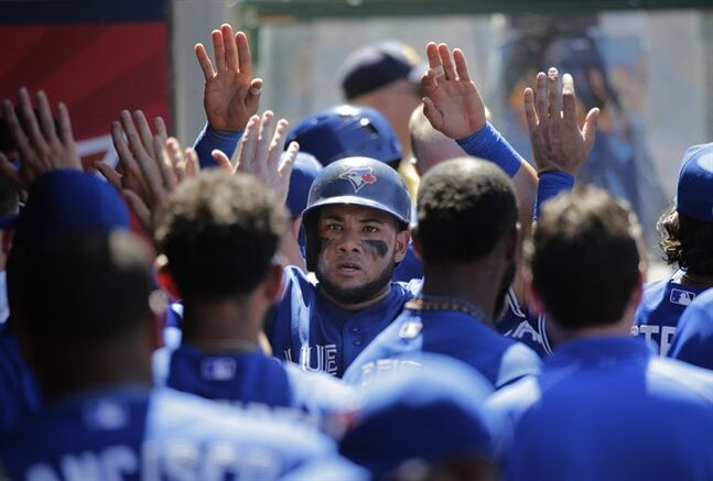 Toronto Blue Jays' Melky Cabrera, center, is congratulated by teammates in the dugout after he scored on a single hit by Dioner Navarro during the sixth inning of a baseball game against the Los Angeles Angels on Wednesday, July 9, 2014, in Anaheim, Calif. (AP Photo/Jae C. Hong)