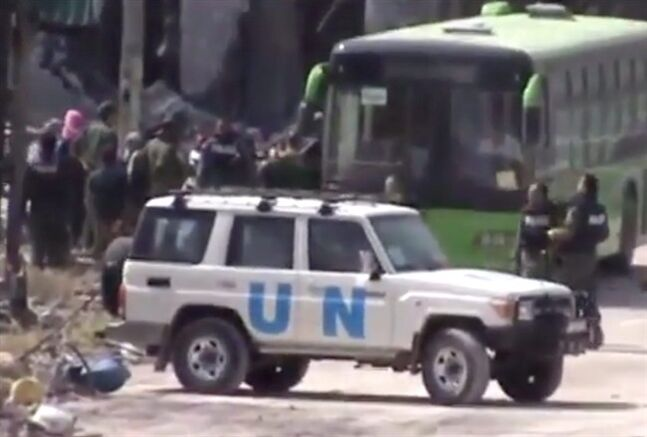 In this image made from amateur video released by Ugarit News, which has been authenticated based on its contents and other AP reporting, Syrian rebels board a bus to leave Homs, Syria, Wednesday, May 7, 2014. Exhausted and worn out from a year-long siege, hundreds of Syrian rebels on Wednesday left their last remaining bastions in the heart of the central city of Homs under a cease-fire deal with government forces. The exit of some 1,200 fighters and civilians will mark a de facto end of the rebellion in the battered city, which was one of the first places to rise up against President Bashar Assad's rule, earning it the nickname of