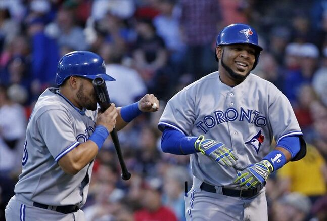 Toronto Blue Jays' Edwin Encarnacion, right, smiles as he is playfully punched by Melky Cabrera after they scored on Encarnacion's two-run homer in the third inning of a baseball game against the Boston Red Sox at Fenway Park in Boston, Tuesday, May 20, 2014. (AP Photo/Elise Amendola)
