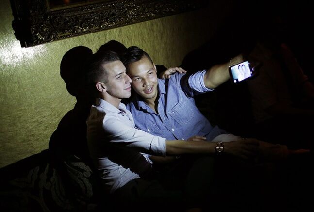 In this June 29, 2014 photo, Philip Noynosoudachanh, right, takes a selfie with Josh Smith at Liaison Nightclub in Bally's Las Vegas early in the morning on Sunday, June 29, 2014 in Las Vegas. Liaison Nightclub, which opened in 2014, is the first gay club inside of a major casino on the Las Vegas Strip. (AP Photo/John Locher)
