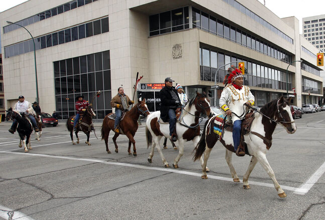 Carl Mazawasicuna with the Sioux Valley Dakota Nation leads a group of supporters across York Ave. to the Law Courts building Monday morning for the court the appearance of Chief Frank Brown and a number of other Dakota who faces a charge of contempt of court . The group rode from The Forks. with story  (WAYNE GLOWACKI/WINNIPEG FREE PRESS) Winnipeg Free Press  Nov.5     2012