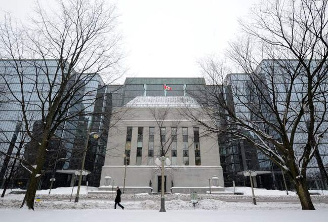 A pedestrian walk along Wellington Street past the Bank of Canada in Ottawa on Tuesday, January 17, 2012.