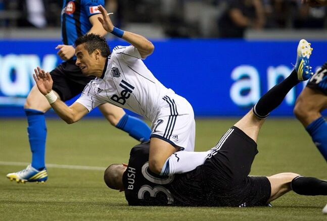 Vancouver Whitecaps' Camilo Sanvezzo, top, of Brazil, collides with Montreal Impact goalkeeper Evan Bush as he makes the save during the first half of the Canadian Championship soccer game in Vancouver, B.C., on Wednesday May 29, 2013. Bush will get the start in goal for the second consecutive game when the Impact, hoping to halt a three-game losing skid, take on Real Salt Lake on Thursday night in Utah. THE CANADIAN PRESS/Darryl Dyck
