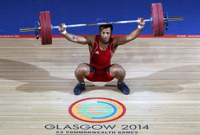 In this image taken Sunday July 27, 2014 Papua New Guinea's Toua Udia competes in the Clean and Jerk of the men's 77kg Weightlifting at the Clyde Auditorium during the 2014 Commonwealth Games in Glasgow Scotland. Toua Udia a weightlifter from Papua New Guinea competed at the Commonwealth Games despite being prosecuted over an alleged sexual assault while in Glasgow. Glasgow Sheriff Court says Toua Udia pleaded not guilty and faces trial on Friday Aug. 1, 2014. Police Scotland said Udia was arrested over the alleged assault after receiving a report of an incident last Monday at a supermarket close to the athletes' village. (AP Photo/Andrew Milligan/PA) UNITED KINGDOM OUT NO SALES NO ARCHIVE