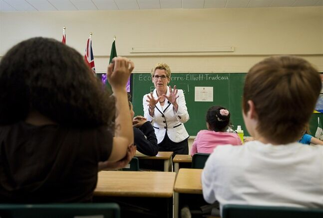 Ontario Premiere Kathleen Wynne, centre, takes questions from students at �cole �l�mentaire Pierre-Elliot-Trudeau school during a campaign stop in Toronto on Friday, May 23, 2014. THE CANADIAN PRESS/Nathan Denette