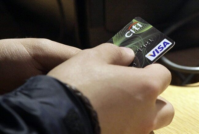 FILE - In this May 9, 2012 file photo, a Visa credit card is tendered at the opening of the Superdry store in New York's Times Square. More than 35 percent of Americans have debts and unpaid bills that have been reported to collection agencies, according to a study released Tuesday, July 29, 2014, by the Urban Institute. (AP Photo/Richard Drew, File)