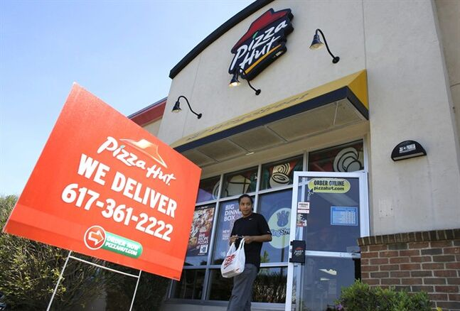 In this Wednesday, May 14, 2014 photo, a customer departs a Pizza Hut restaurant location, in Boston. Yum Brands, parent company of Pizza Hut, Taco Bell, and KFC, reports quarterly financial results on Wednesday, July 16, 2014. (AP Photo/Steven Senne)