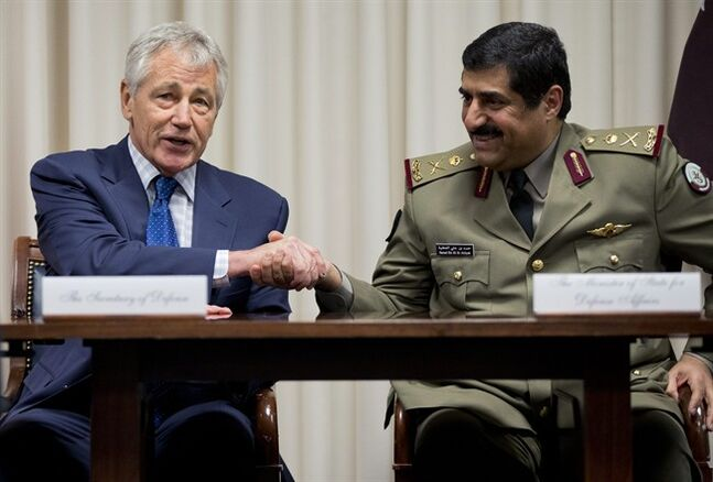 Defense Secretary Chuck Hagel, left, shakes hands with Qatari Defense Minister Hamad bin Ali al-Attiyah, at the Pentagon, Monday, July 14, 2014, during a signing ceremony. (AP Photo/Manuel Balce Ceneta)