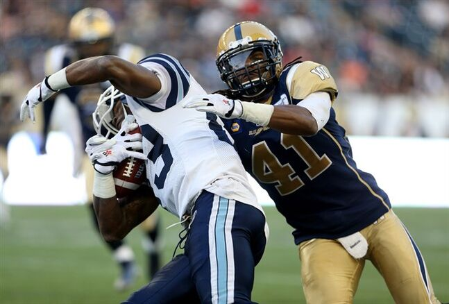 Toronto Argonauts' Terrell Sinkfield (83) spins off of Winnipeg Blue Bombers' Don Unamba (41) during the first half of preseason CFL football action at Investors Group Field in Winnipeg, Monday, June 9, 2014. The CFL and its players will conduct their ratification votes on a new labour deal later this week.Independent league sources requesting anonymity say the players will vote Thursday while the CFL's board of governors will do so Friday. THE CANADIAN PRESS/Trevor Hagan