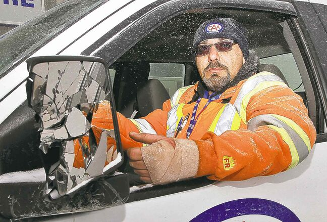 CAA driver Jeff Laufer shows his shattered window and injured hand from when a passing truck clipped his vehicle.