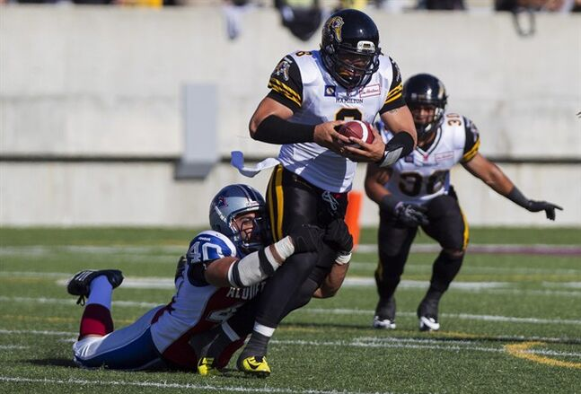 Hamilton Tiger-Cats quarterback Jeremiah Masoli, centre, attempts to shake off the tackle from Montreal Alouettes' Ameet Pall during pre-season CFL action in Hamilton, Ont., Saturday, June 14, 2014. THE CANADIAN PRESS/Aaron Lynett