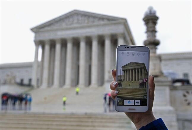 FILE - In this Tuesday, April 29, 2014 file photo, a Supreme Court visitor takes pictures with her cell phone outside the Supreme Court in Washington, during a hearing to consider whether police may search cell phones found on people they arrest without first getting a warrant. The Supreme Court ruling barring police from searching cell phones without a warrant had an immediate impact as police nationwide were briefed during roll calls, new procedures were issued and prosecutors discussed the potential impact to possibly thousands of pending court cases. From Los Angeles to New York, and in San Diego, Chicago and Houston, departments met to discuss the unanimous ruling issued Wednesday, June 25, 2014, that prohibits law enforcement from searching an arrestees' cell phone without a warrant unless a person's safety or life may be in danger and could make it harder for officers to quickly find incriminating evidence. (AP Photo/Jose Luis Magana, file)