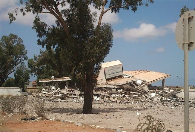 A criminal evidence building is seen collapsed after an attack by Islamic hard-line militias in Benghazi, Libya, Friday, Aug. 1, 2014. Islamic hard-line militias, including the group accused by the United States in a 2012 attack that killed the ambassador and three other Americans, claimed control of Libya's second largest city, Benghazi, after overrunning army barracks and seizing heavy weapons. (AP Photo)